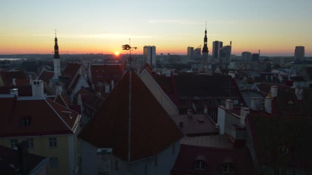 The sun rises over the Baltic Sea beyond historical buildings standing in the Old Town on the city skyline in Tallinn Estonia on Tuesday March 17 2015
