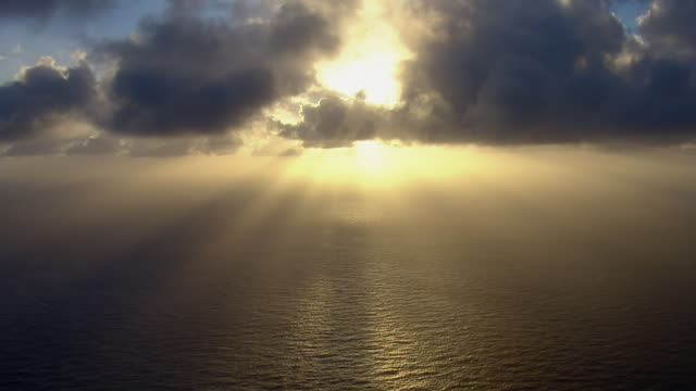 the sun rises over the pacific ocean, sending rays of light across the water's surface and piercing a mass of thick clouds. - aircraft point of view stock videos & royalty-free footage