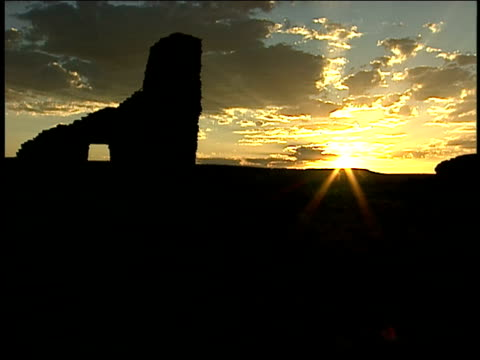 the sun rises over the silhouetted ruins of chaco canyon's pueblo del arroyo. - chaco canyon stock videos & royalty-free footage