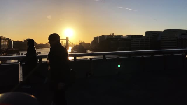 The sun rises over Tower Bridge as commuters cross London Bridge at the start of the working day on February 16 2018 in London England