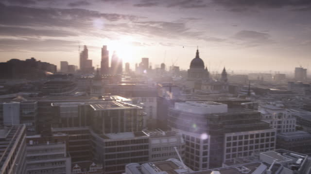 The sun rises through the clouds that hang over the London skyline.