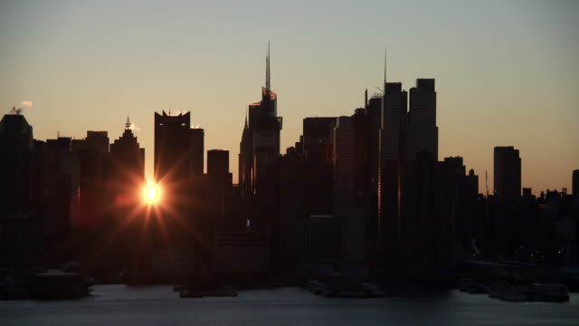 the sun rising between two skyscrapers against the silhouette of the new york city skyline near the chrysler building and the bank of america tower - chrysler building stock videos & royalty-free footage