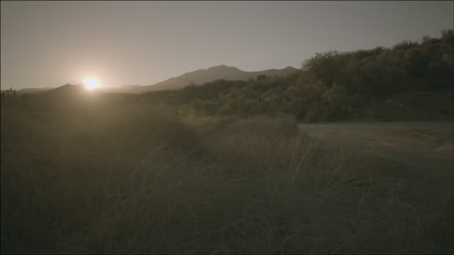 WS The sun rising over a desert mountain landscape / Acton, California, United States