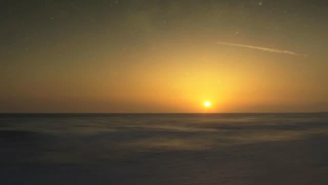 vídeos y material grabado en eventos de stock de the sun sets and stars appear over a calm, undulating ocean. - aumento digital
