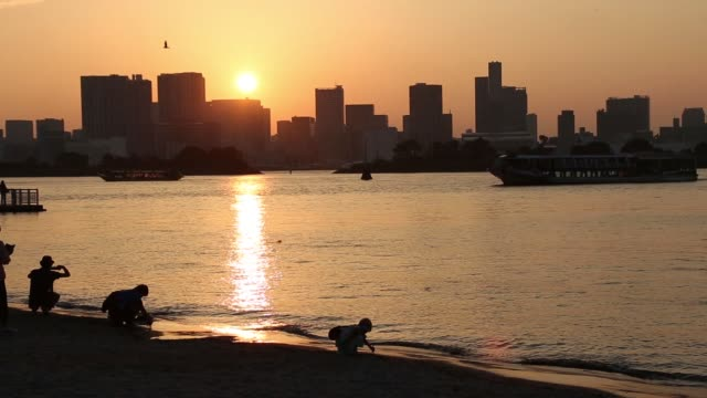 The sun sets as children are silhouetted along the shore of Odaiba beach in Tokyo Japan on Monday Sept 28 Silhouetted people watch the setting sun on...
