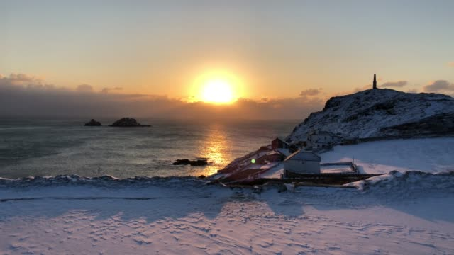 the sun sets as snow covers the fields surrounding cape cornwall near penzance on february 28 2018 in cornwall england freezing weather conditions... - cornwall england stock videos and b-roll footage