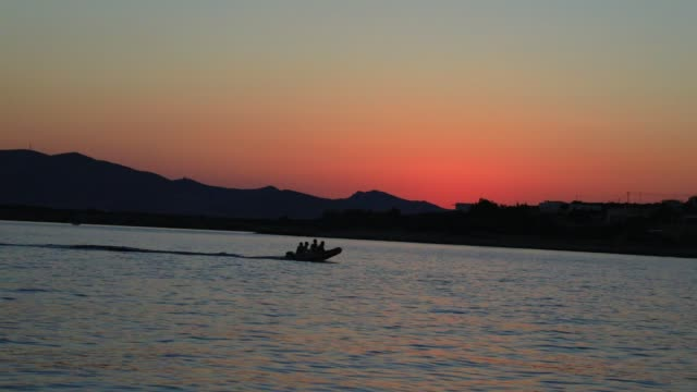 the sun sets behind a motorboat on august 19, 2020 in parikia, greece. the island of paros has seen increasing tourist numbers in recent years being... - atmosphere filter stock videos & royalty-free footage
