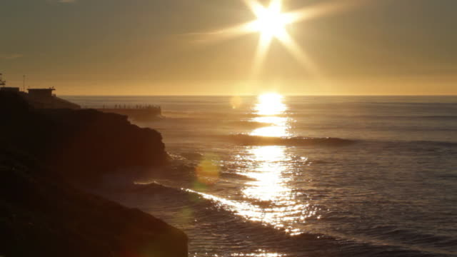 The sun sets behind a sandy beach in La Jolla, California.