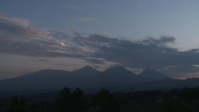 The sun sets behind a volcano in the Volcanoes National Park of Rwanda. Available in HD.