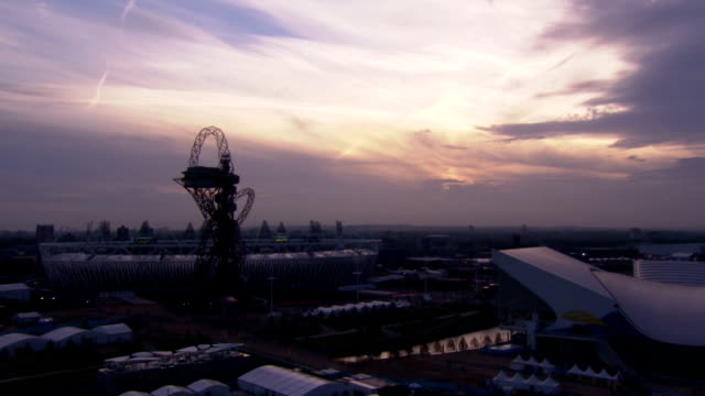 the sun sets behind dark clouds overlooking the london 2012 olympic park, leaving an orange hue in the sky time-lapse olympic park dusk at olympic... - 2012 stock videos & royalty-free footage
