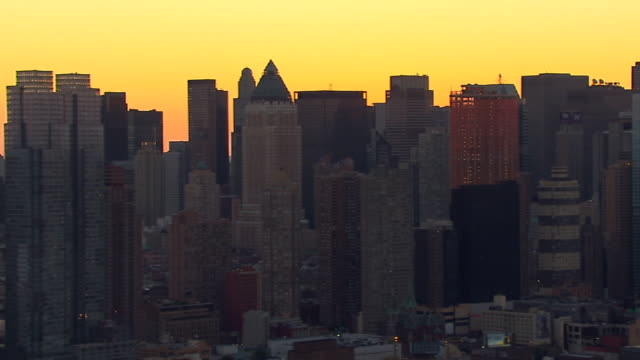 the sun sets behind manhattan skyscrapers. - skyscraper stock videos & royalty-free footage
