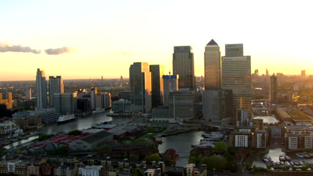 The sun sets behind One Canada Square in London's Canary Wharf financial district.