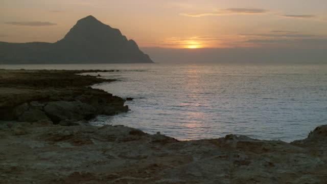 the sun sets behind the mediterranean sea near a coastal mountain in sicily, italy. - mar mediterraneo video stock e b–roll