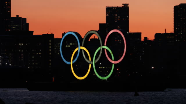the sun sets behind the olympic rings in odaiba marine park on march 24 2020 in tokyo japan although an official decision is yet to be announced... - tokyo japan stock videos & royalty-free footage