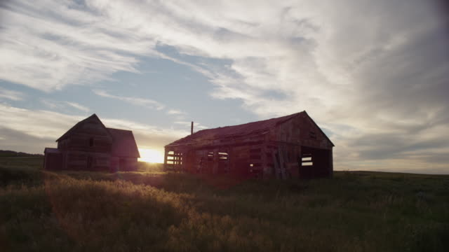 stockvideo's en b-roll-footage met the sun sets behind the ruins of an abandoned, gray-weathered barn and homestead on the high desolate plains. - boerderijschuur