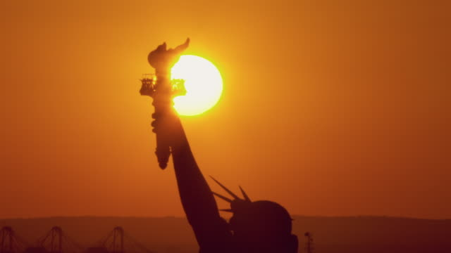 the sun sets behind the statue of liberty's torch. - statue of liberty new york city stock videos & royalty-free footage