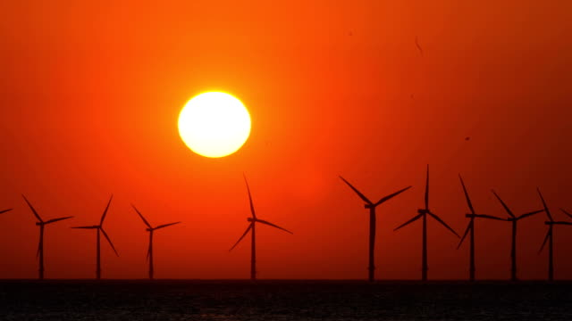 the sun sets behind the wind turbines of burbo bank offshore wind farm in the irish sea on may 23 2018 in wallasey england - filmset stock-videos und b-roll-filmmaterial