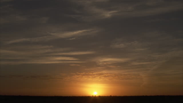 the sun sets on the horizon in australian outback. - horizont über land stock-videos und b-roll-filmmaterial