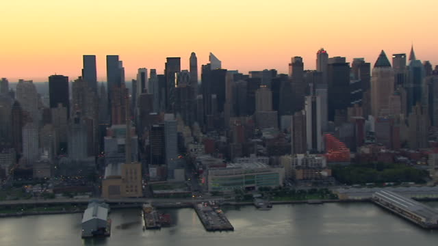 the sun sets over new york harbor and the manhattan skyline. - new york harbor stock videos & royalty-free footage