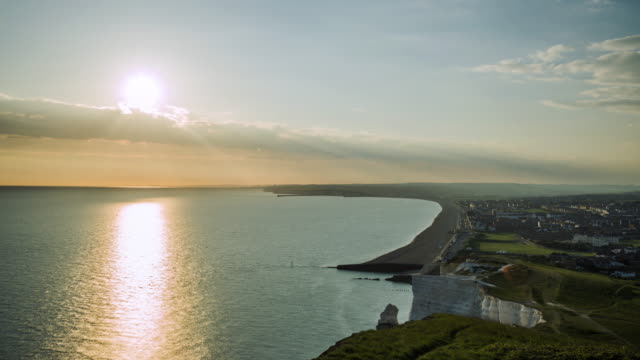 The sun sets over the English Channel and small seaside town of Seaford on the south coast of England