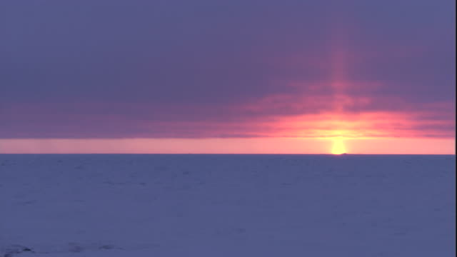 The sun sets over the frozen tundra of Arctic Canada. Available in HD.
