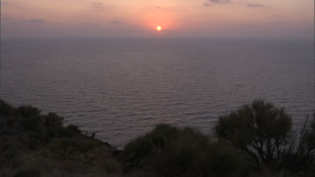 The sun sets over the ocean by the shores of Stromboli. Available in HD.