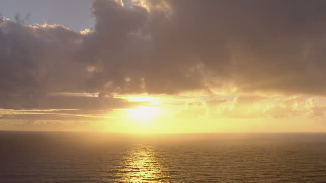 The sun sets over the Pacific Ocean, casting golden light across the water's surface.