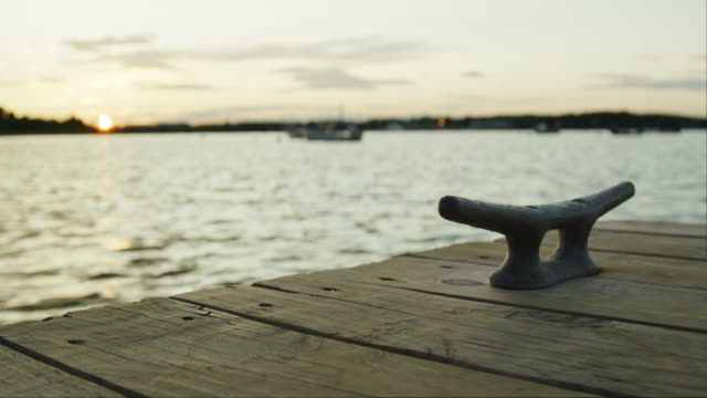 die sonne geht über dem meer und ein bootsdock mit einem metall-dock cleat beim east end boat launch in portland, maine (atlantik) - ruhige szene stock-videos und b-roll-filmmaterial