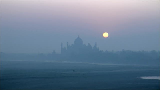 the sun sets over the taj mahal in india. - architectural feature stock videos & royalty-free footage