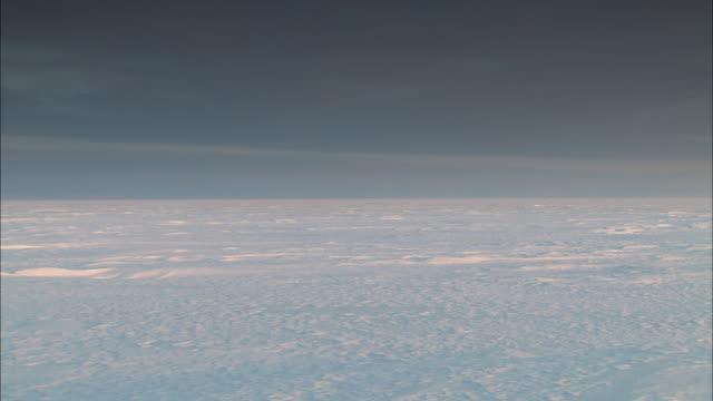 The sun sets over the vast, desolate Alaskan tundra.