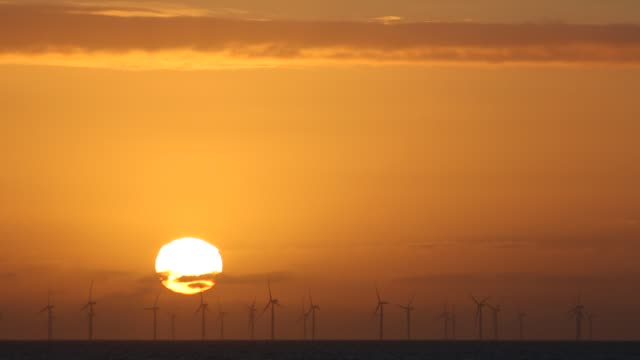 the sun setting behind the walney offshore wind farm taken from walney island, cumbria, uk. - glowing stock videos & royalty-free footage