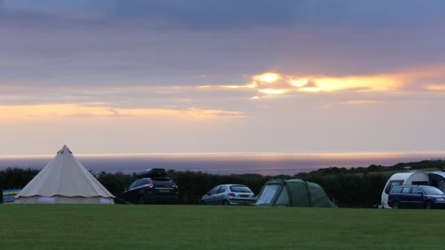 the sun setting over the cornish coast from a campsite in st agnes, united kingdom on august 20, 2015. - glowing stock videos & royalty-free footage