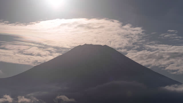 the sun setting towards mt. fuji with iridescent clouds (time lapse/tilt down) - light natural phenomenon stock videos & royalty-free footage