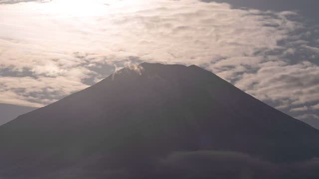 the sun setting towards the summit of mt. fuji over iridescent clouds (timelapse/zoom in) - light natural phenomenon stock videos & royalty-free footage