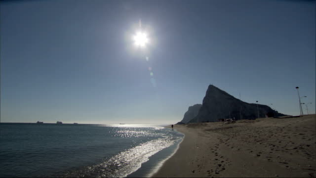 stockvideo's en b-roll-footage met the sun shines above a tranquil beach in gibraltar. available in hd. - gibraltar iberisch schiereiland