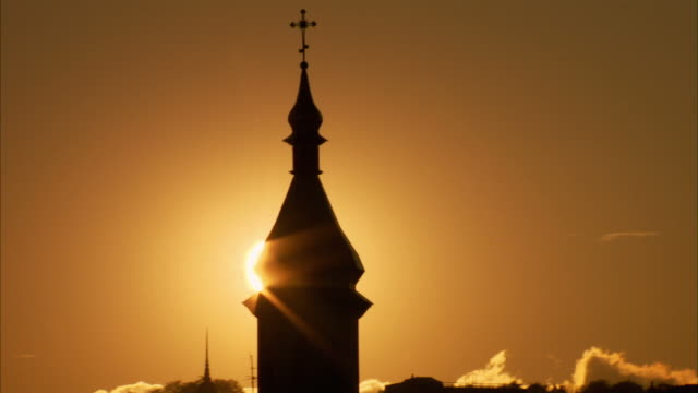 the sun shines around a church spire at golden hour. available in hd. - russia stock videos & royalty-free footage