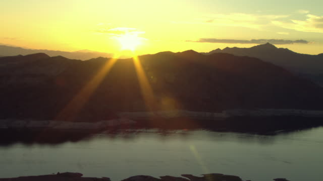 the sun shines behind mountains surrounding lake mead. - lake mead video stock e b–roll