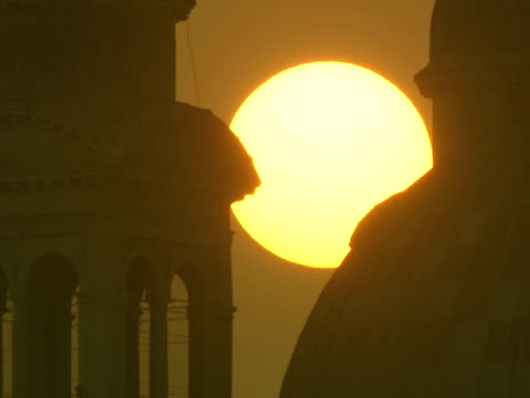 vidéos et rushes de the sun shines between a large dome and tower in venice, italy. - venise