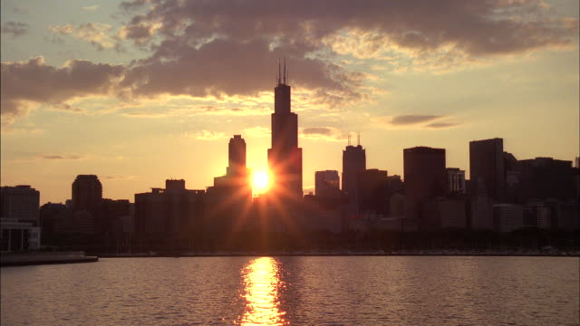 vídeos de stock e filmes b-roll de the sun shines between skyscrapers in the chicago skyline. - ano 2000