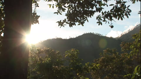 the sun shines bright over forested hills. - twilight stock videos & royalty-free footage