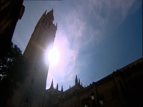 the sun shines down on a cathedral tower at golden hour. - golden hour stock videos & royalty-free footage