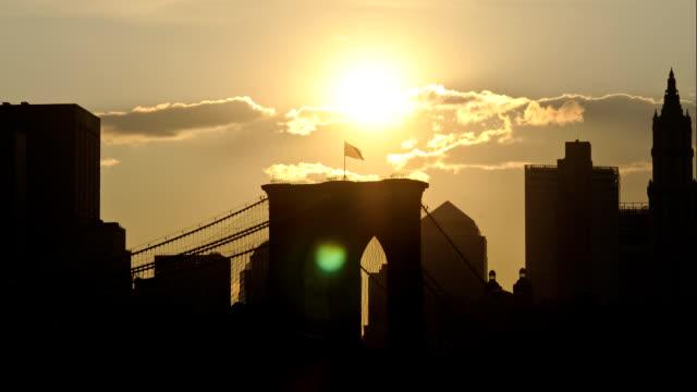 The sun shines down on the Brooklyn Bridge through drifting clouds.