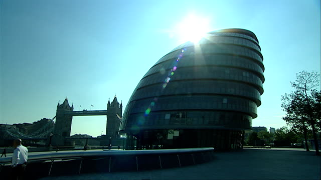 the sun shines from behind london city hall. available in hd. - gla building stock videos & royalty-free footage