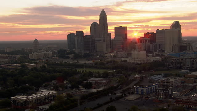 the sun shines from behind the charlotte, north carolina skyline. - charlotte north carolina stock videos & royalty-free footage