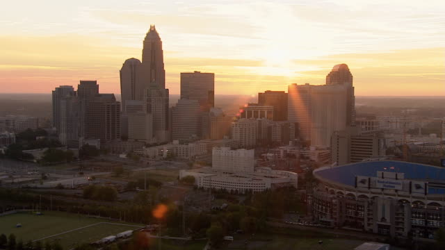 the sun shines from behind the charlotte skyline. - charlotte north carolina stock videos & royalty-free footage