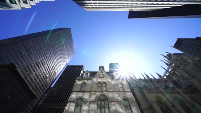 the sun shines from interval of the tips of the st. patrick's cathedral among the midtown manhattan skyscrapers at new york ny usa on apr. 21 - st. patrick's cathedral manhattan stock videos and b-roll footage