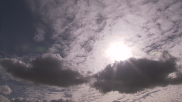 The sun shines in a cloudy sky.
