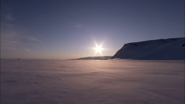 the sun shines on a frozen tundra in the arctic circle. available in hd. - arctic stock videos and b-roll footage