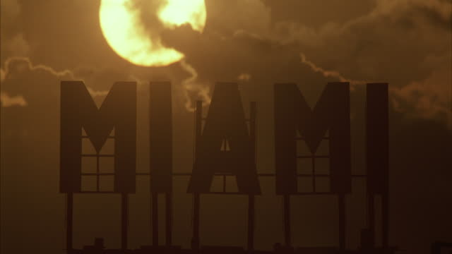 The sun shines on a sign that reads Miami.
