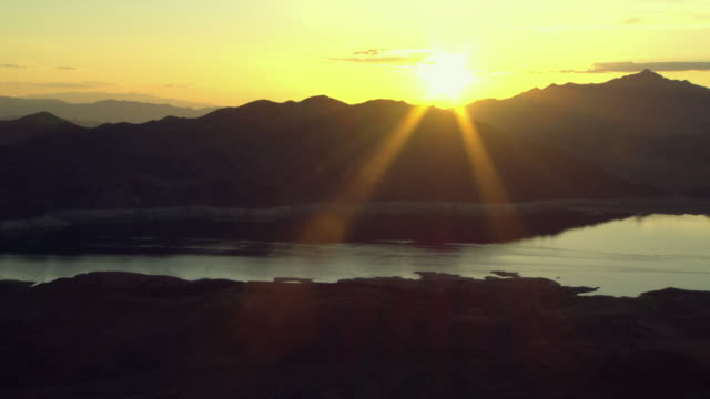 the sun shines on lake mead over silhouetted mountaintops. - lake mead video stock e b–roll